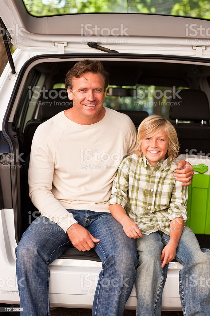 Father and son sitting at the hatchback of a car royalty-free stock photo