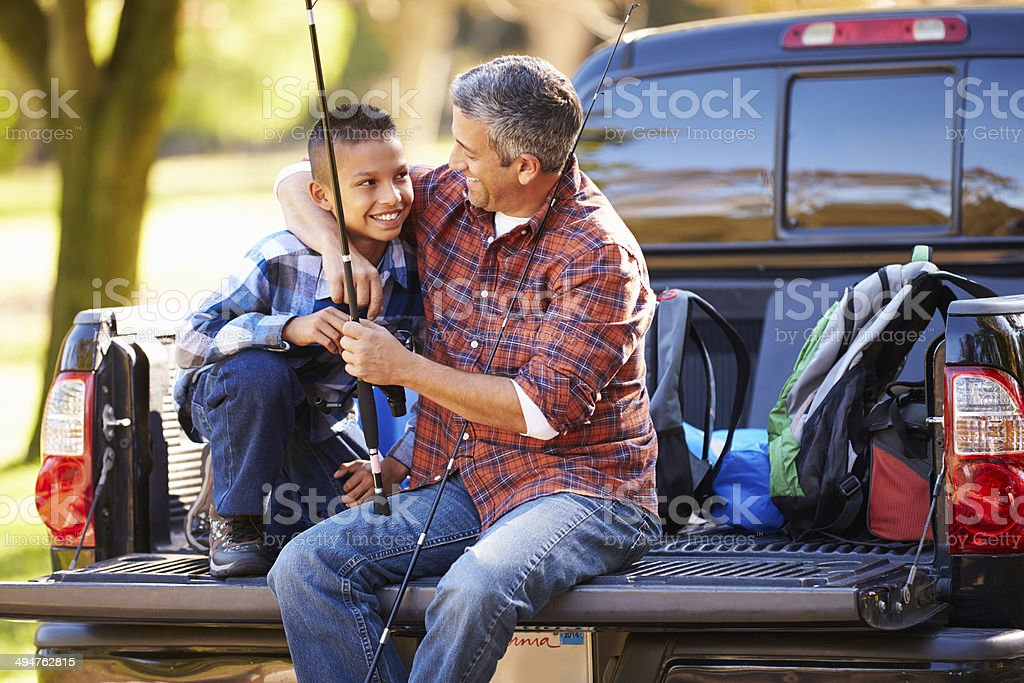 Father And Son Sitting In Pick Up Truck Camping Holiday stock photo