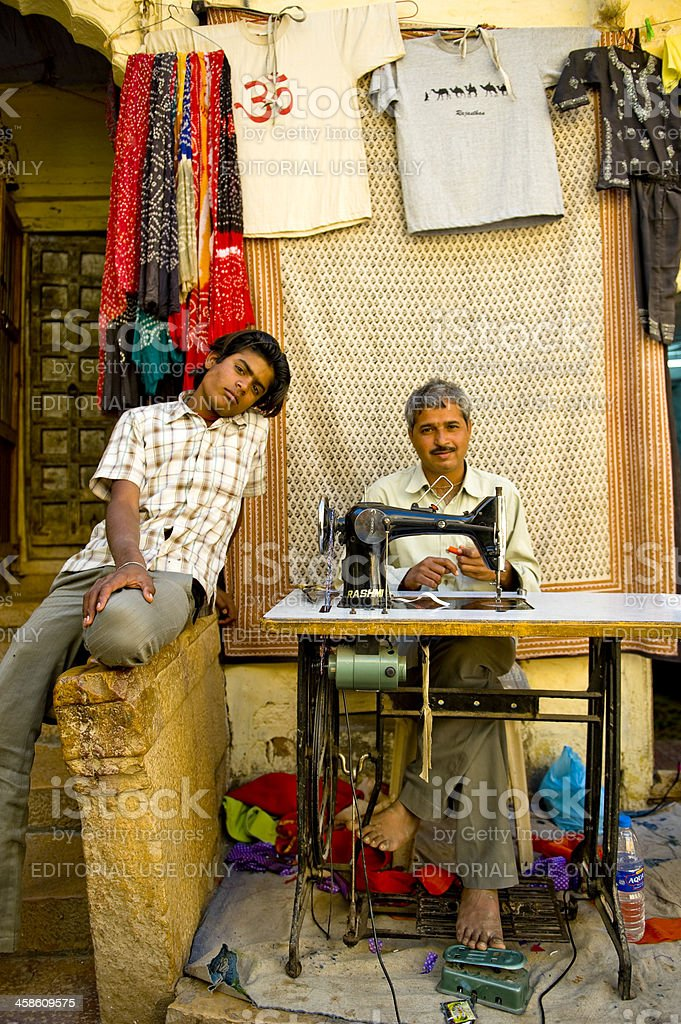 Father and son sitting in their tailor's shop stock photo