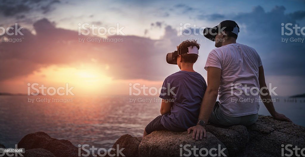 Father and son sitting in VR glasses outside at sunset stock photo