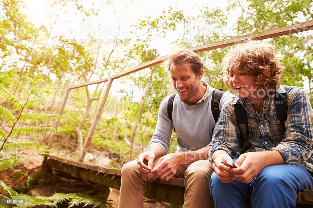 Father and son sitting on a bridge in forest stock photo