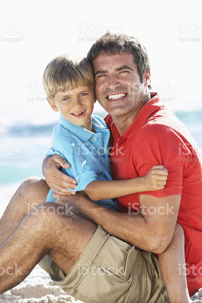 Father And Son Sitting On Beach stock photo