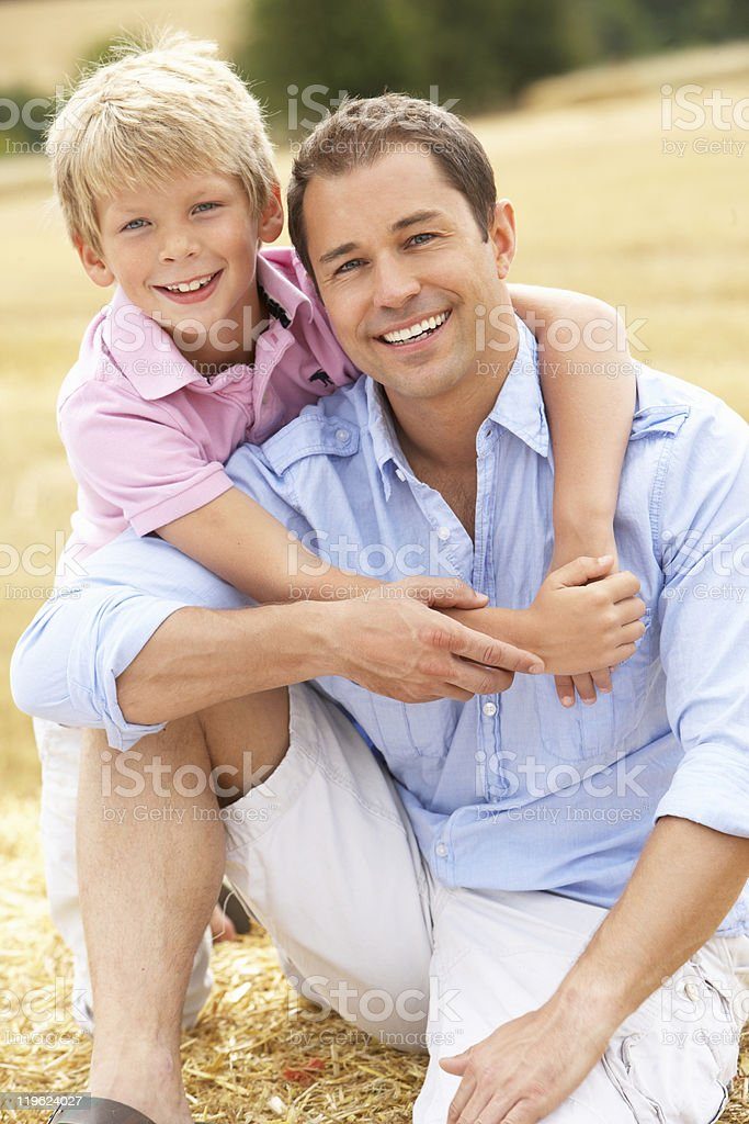 Father And Son Sitting On Straw Bales In Field stock photo