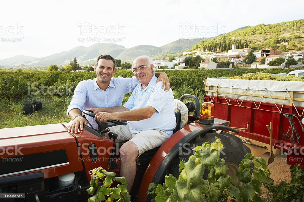 Father and son sitting on tractor stock photo