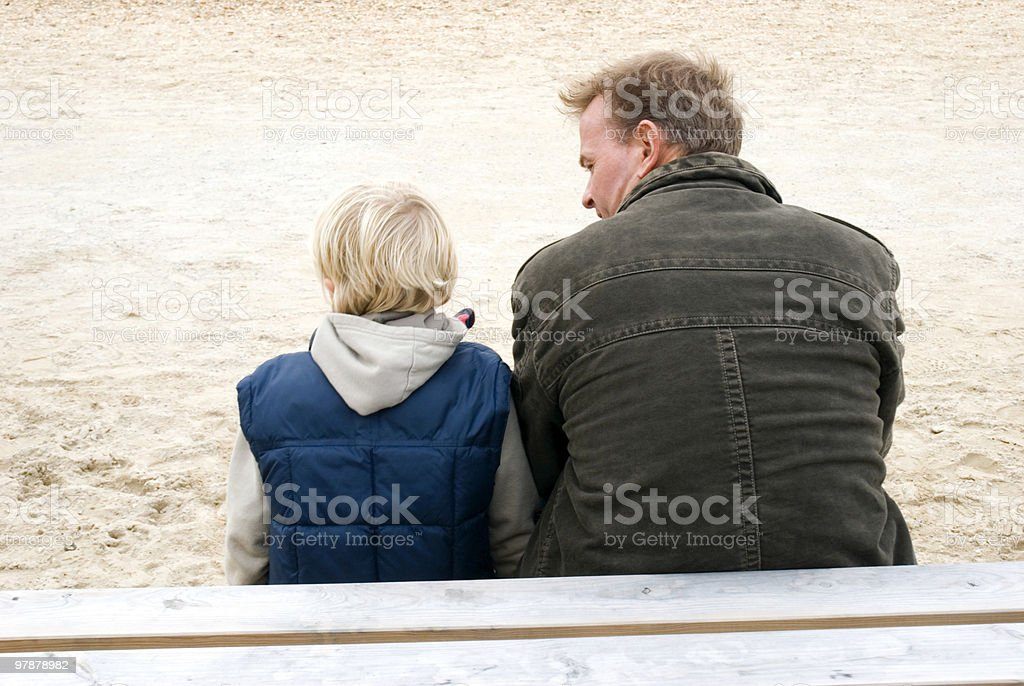 father and son sitting together royalty-free stock photo