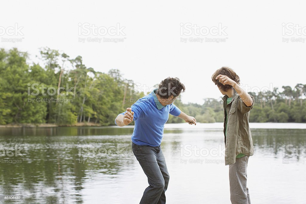 Father and son skimming stones in lake stock photo