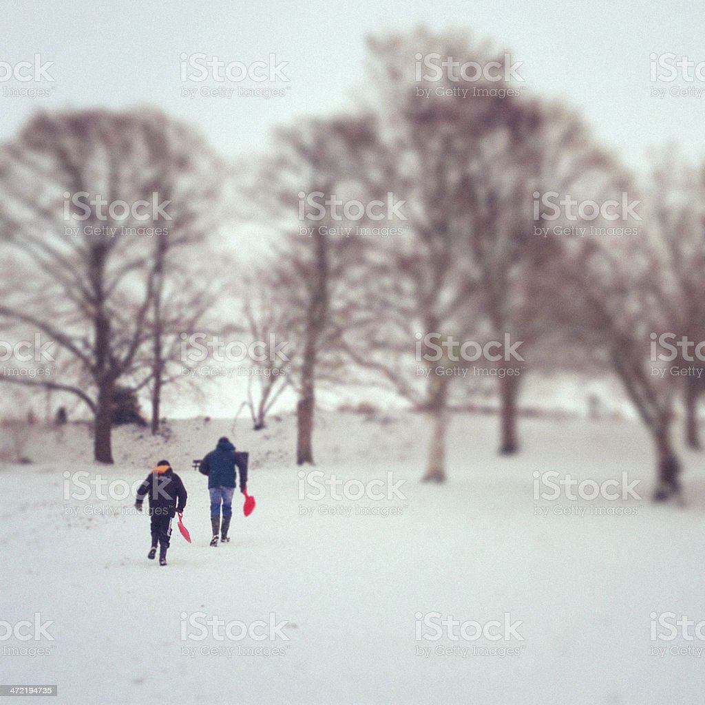 Father and son sledding in snow stock photo