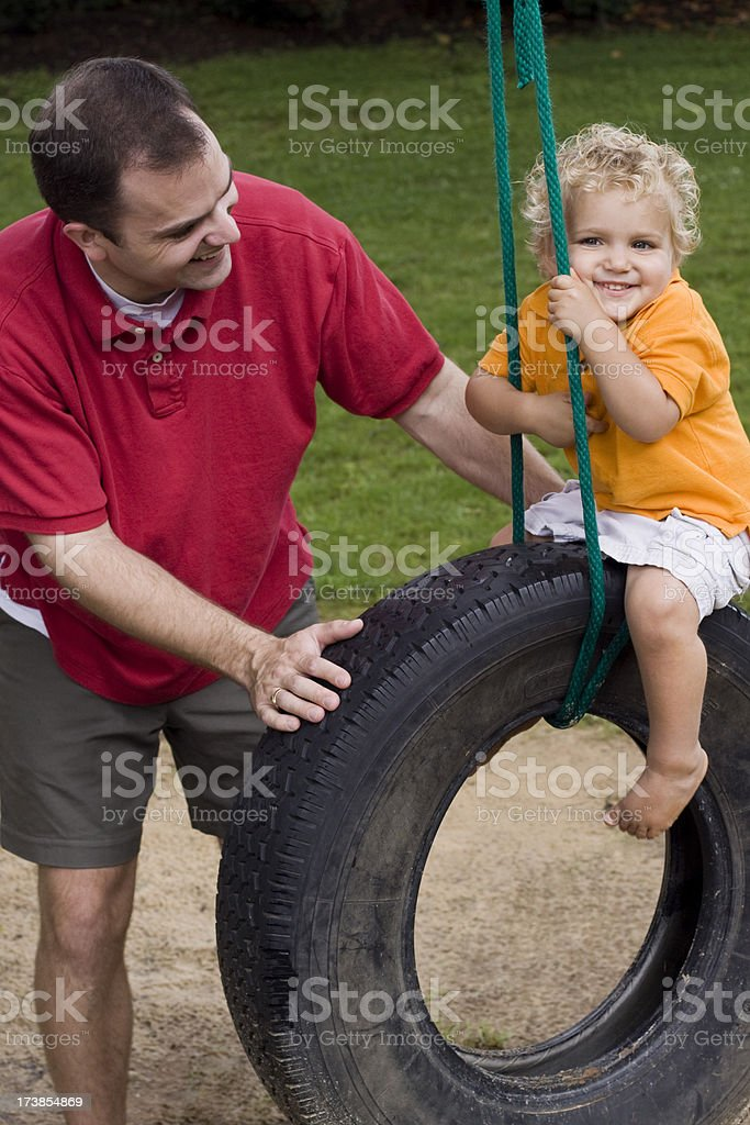 father and son spending time together on tire swing. royalty-free stock photo