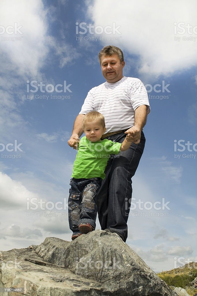 Father and Son standing at the edge of rock royalty-free stock photo