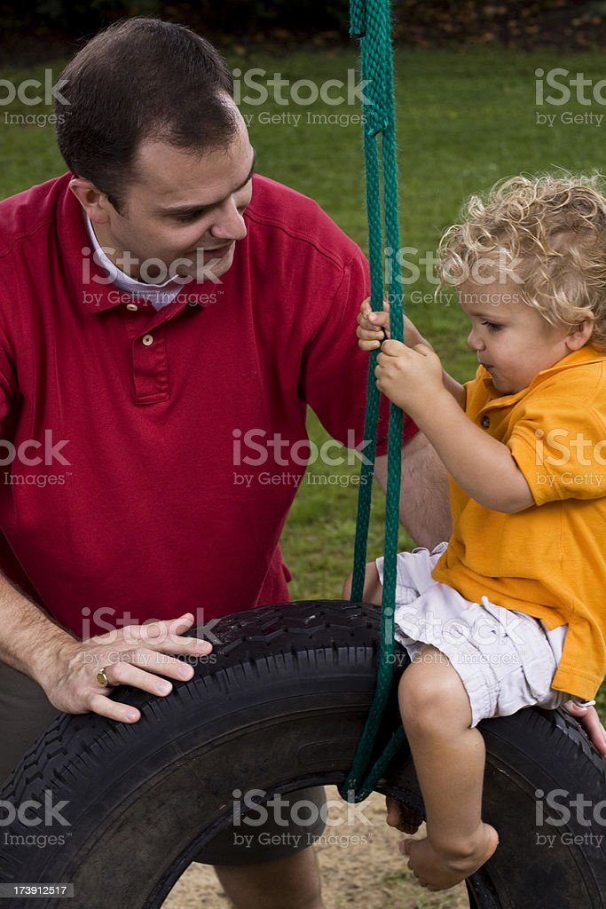 Father and son swinging on tire swing together stock photo