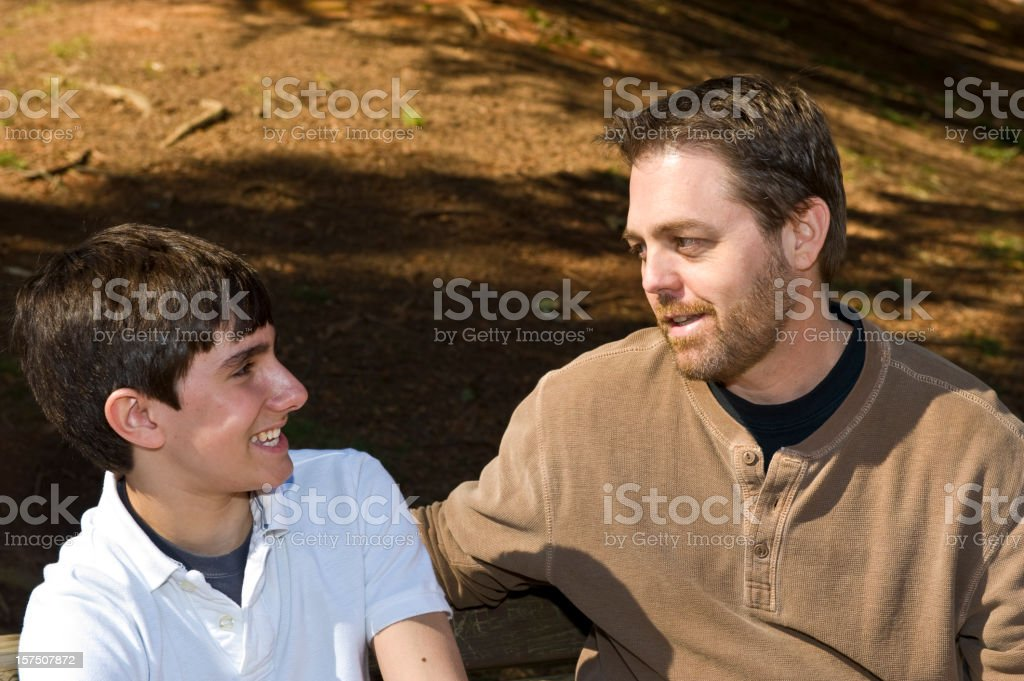 Father and Son Talking on a Bench in Park royalty-free stock photo