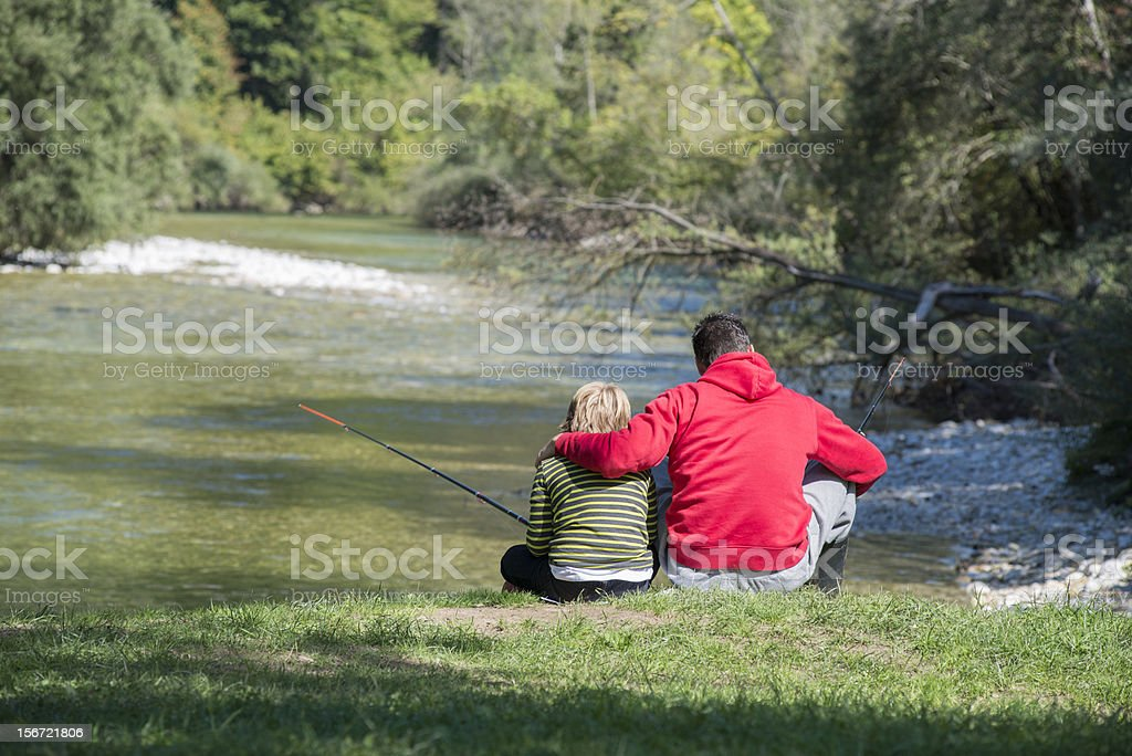 Father and son together by the river royalty-free stock photo