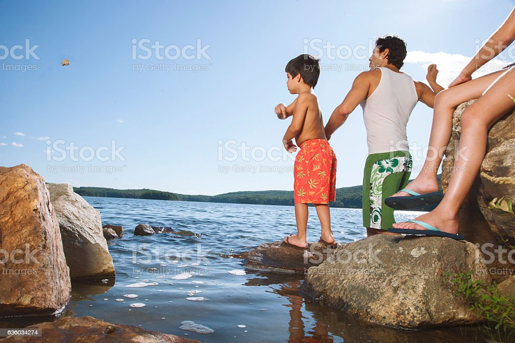 Father and son tossing rocks into lake stock photo