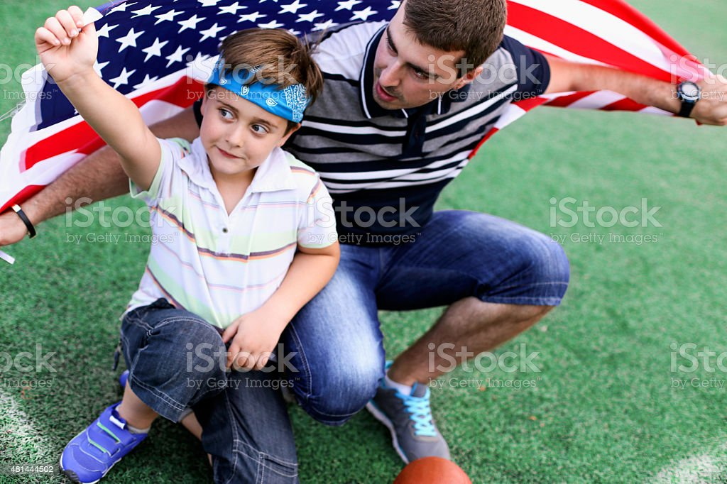father and son under American flag at stadium stock photo