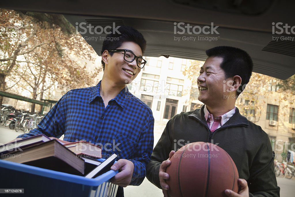 Father and Son unpacking car in front of dormitory stock photo