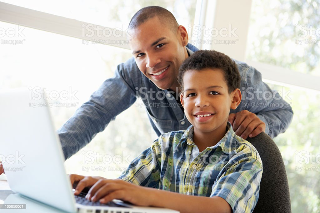 Father And Son Using Laptop At Home stock photo