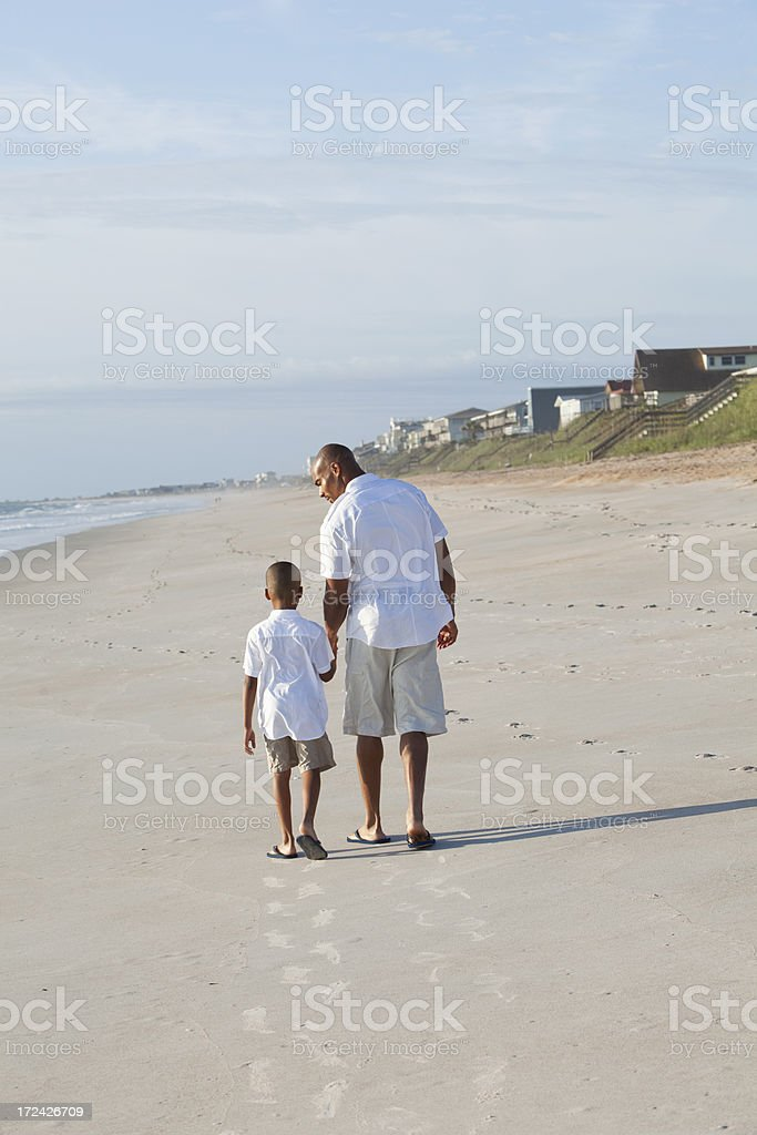 Father and son walking at the beach stock photo