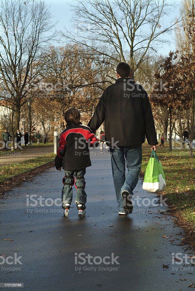 Father and son walking away seen on back royalty-free stock photo