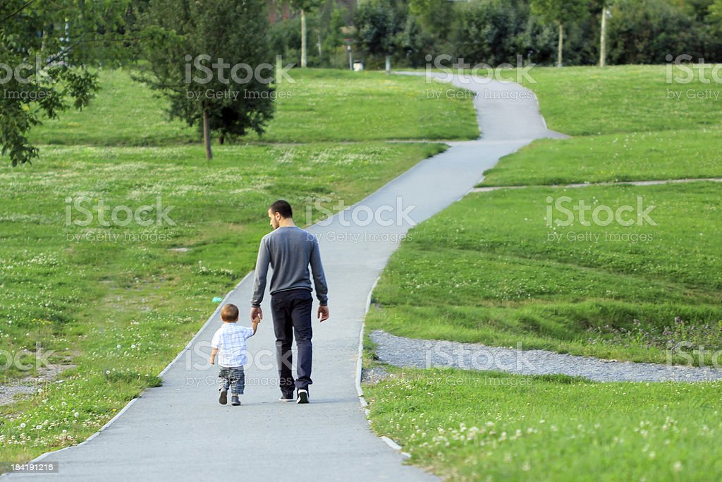 Father and son walking in a park royalty-free stock photo