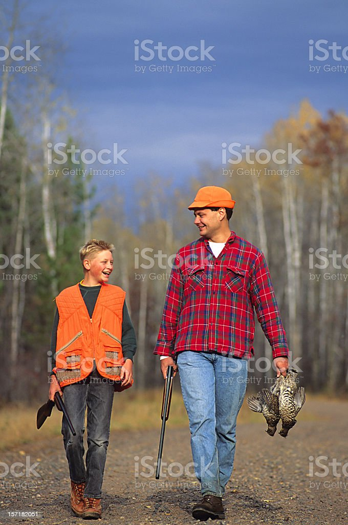 Father and son walking outdoors in hunting gear  stock photo