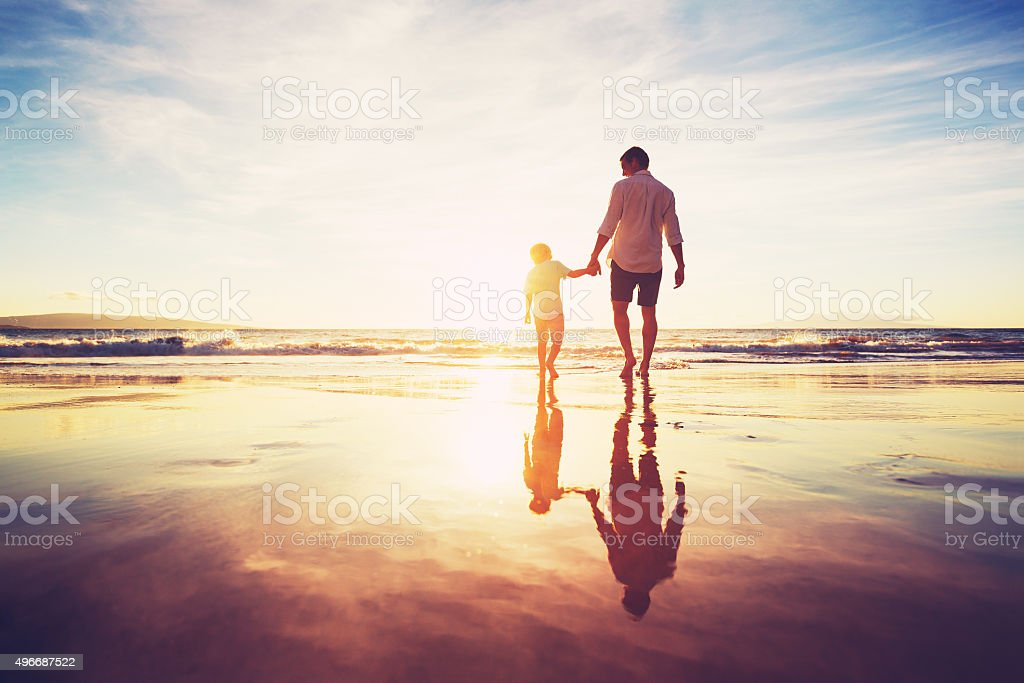 Father and Son Walking Together Holding Hands stock photo