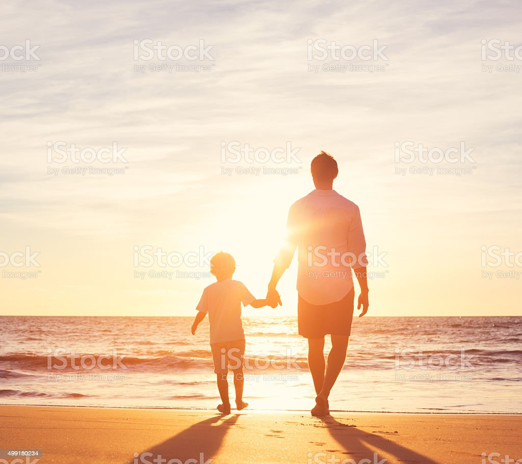 Father and Son Walking Together on the Beach stock photo