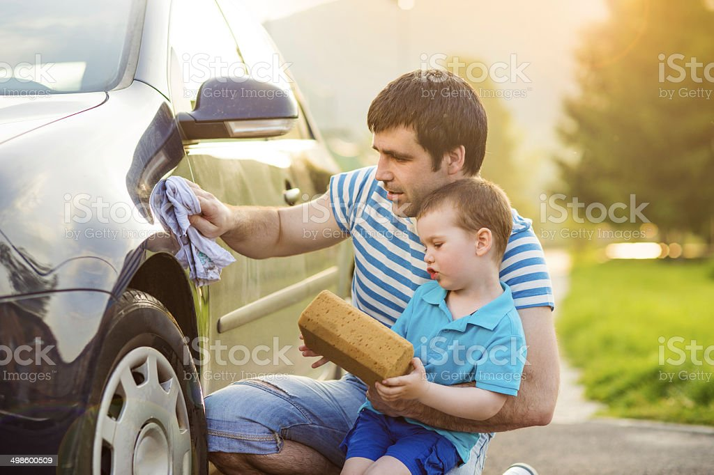 Father and son washing car stock photo