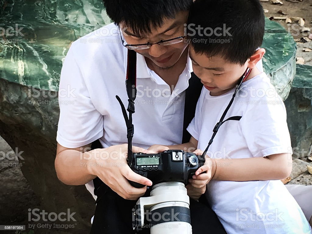 Father and son watch camera together stock photo