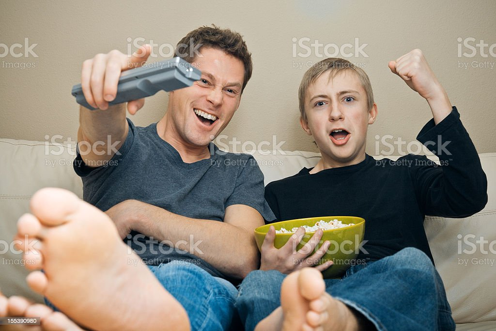 Father and Son Watching Exciting Sports Show royalty-free stock photo