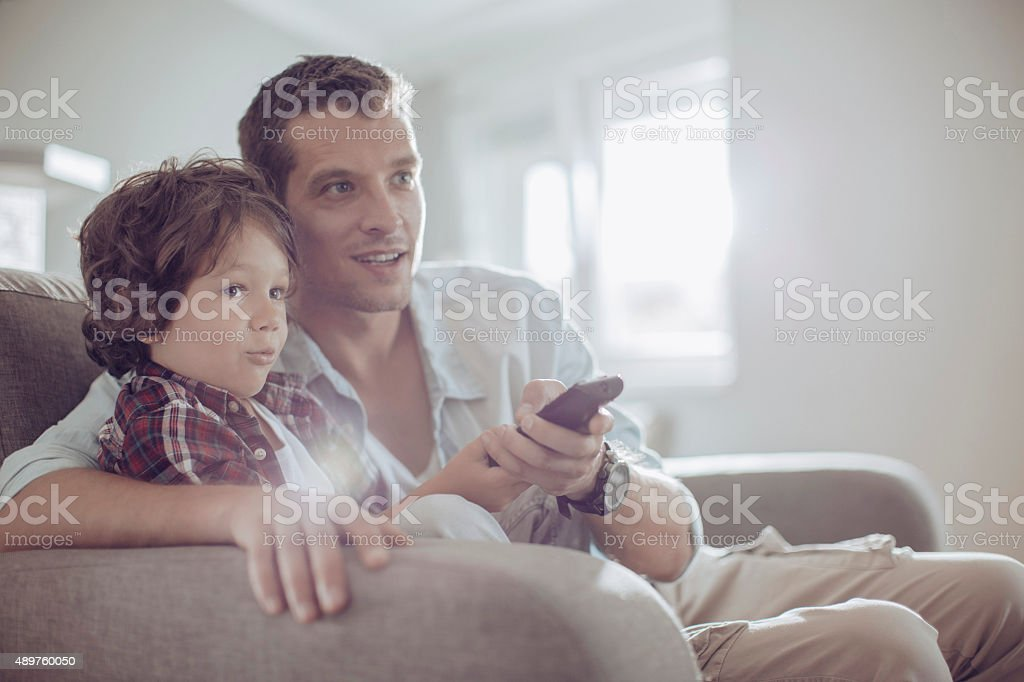 Father and son watching football stock photo