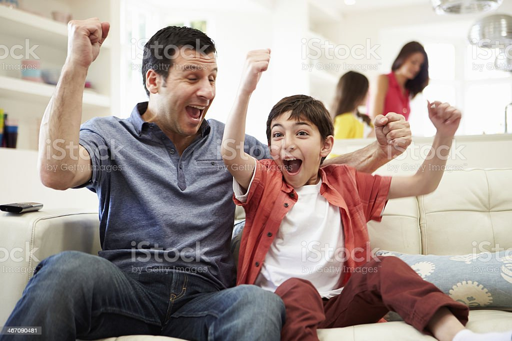 Father And Son Watching Sports On TV stock photo