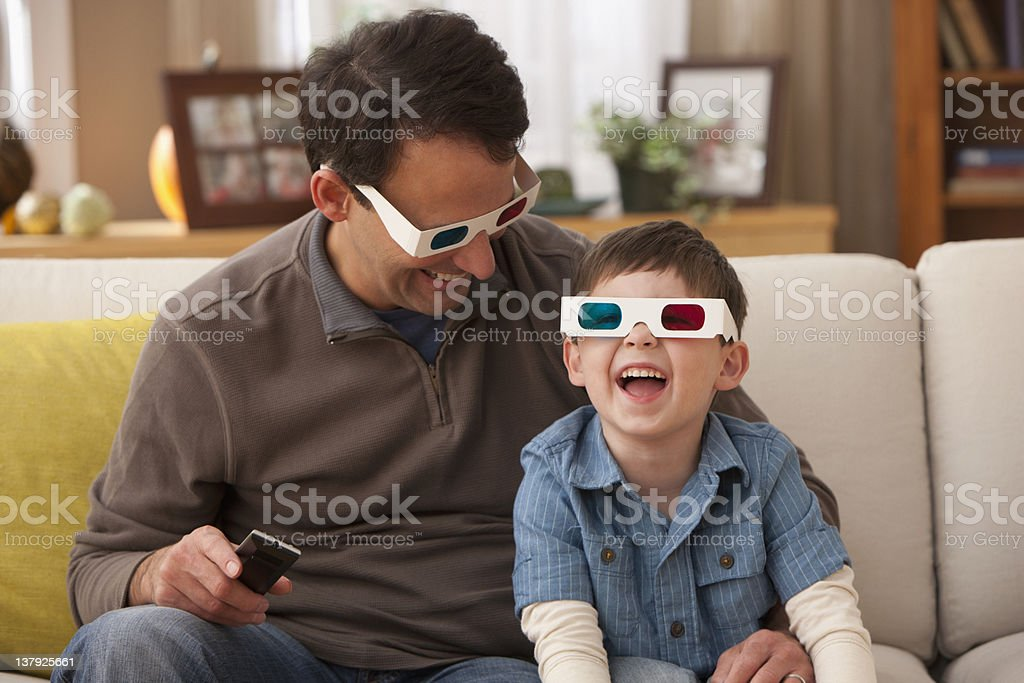 Father and son watching television with 3D glasses stock photo