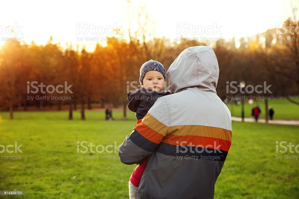 Father and son watching the sunset in the autumn nature. stock photo