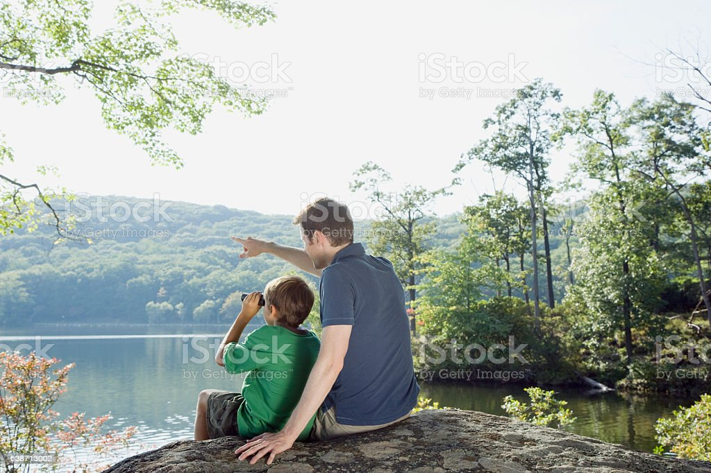 Father and son with binoculars looking at view in nature stock photo