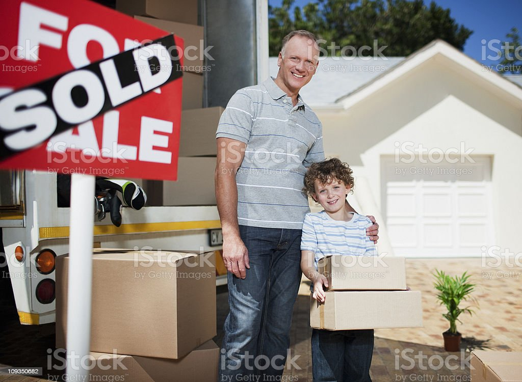 Father and son with boxes standing near sold sign for their new house royalty-free stock photo