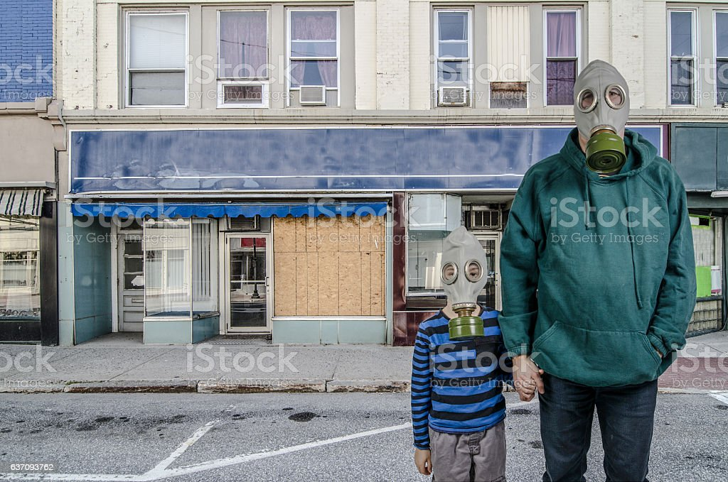 Father and son with gas mask front of abandoned store stock photo