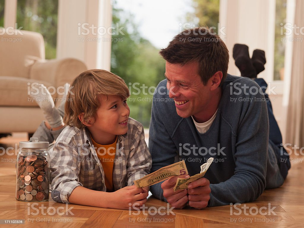 Father and son with paper currency stock photo