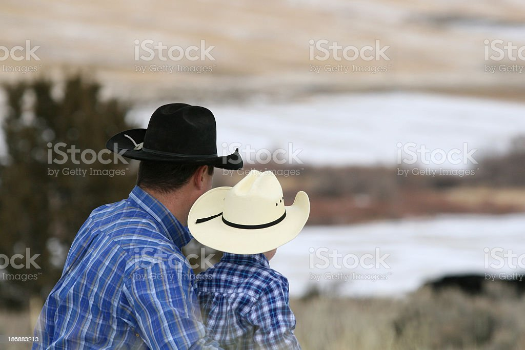 Father and son with plaid shirts and cowboy hats stock photo