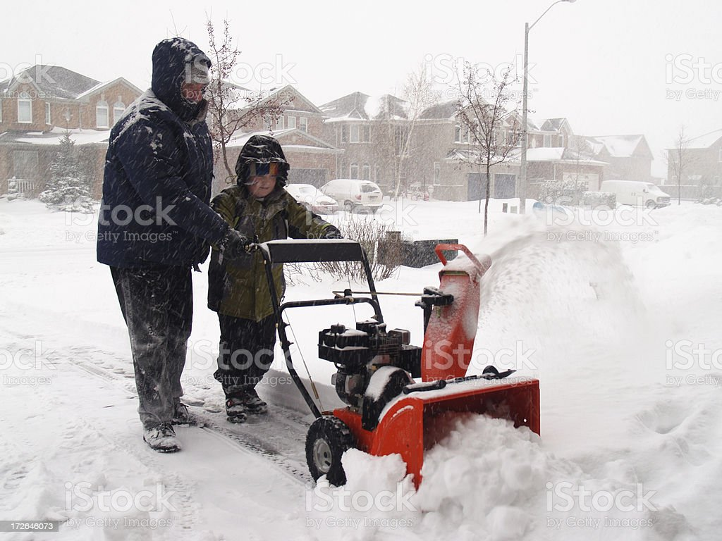 Father and son with snowblower stock photo