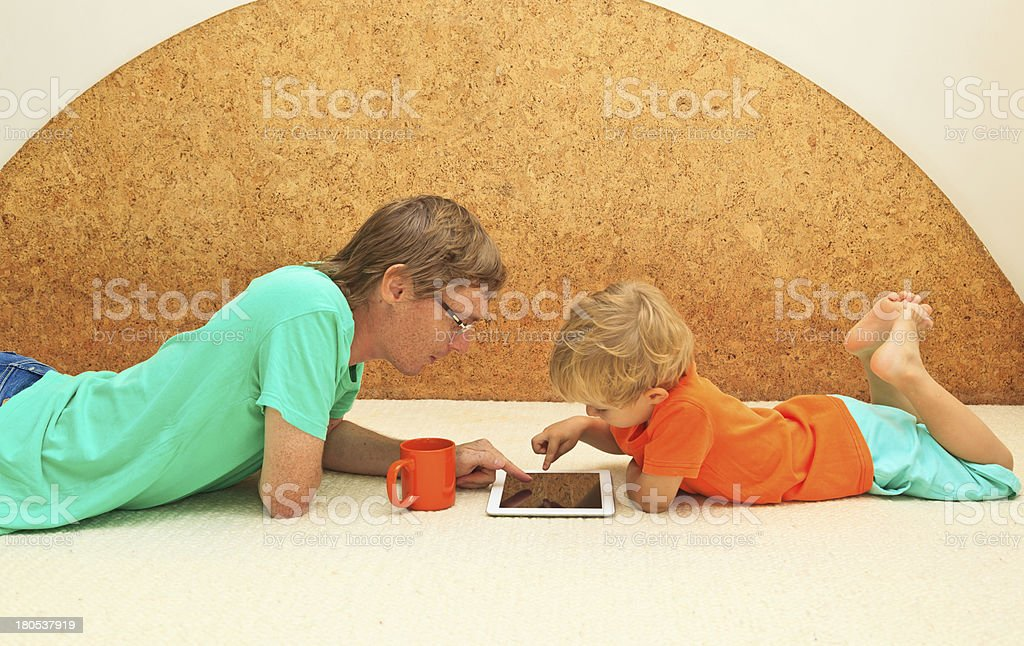 father and son with touch pad at home royalty-free stock photo