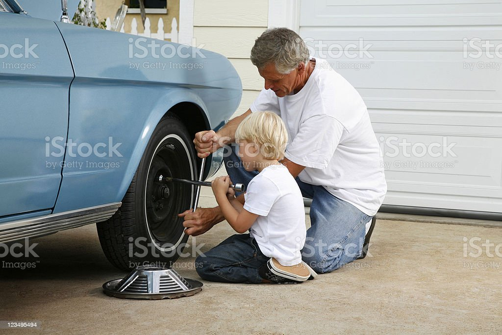 father and son working on the car stock photo