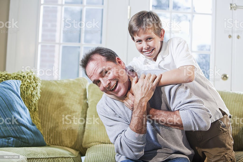 Father and son wrestling on couch royalty-free stock photo