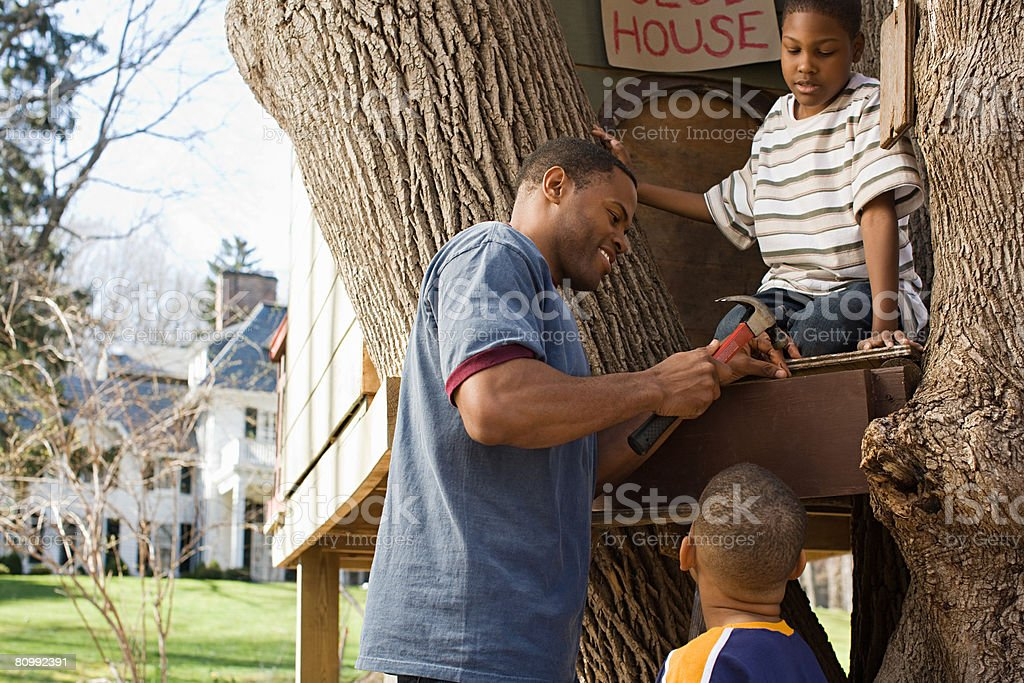 Father and sons building tree house stock photo