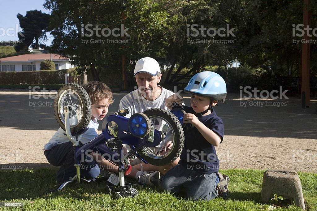 Father and sons fixing bike royalty-free stock photo