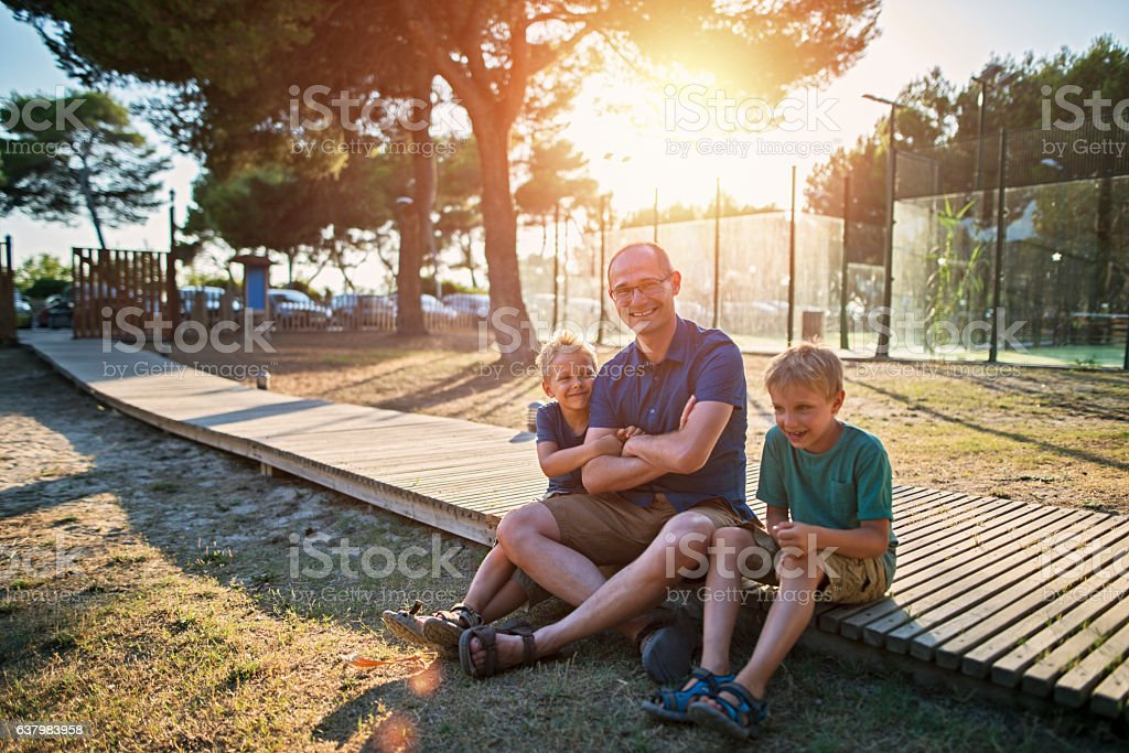 Father and sons hanging out in the park stock photo