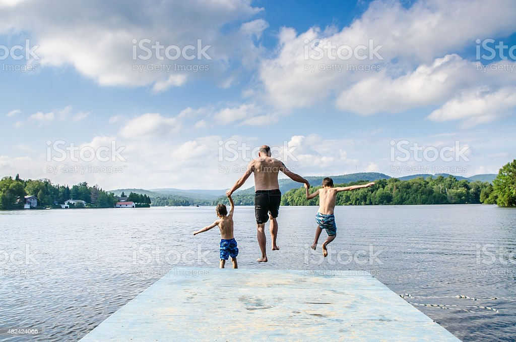 Father and sons jumping in lake stock photo