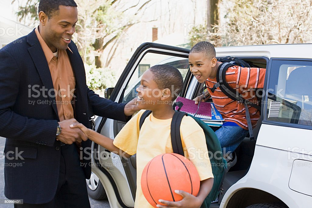 Father and sons leaving car stock photo