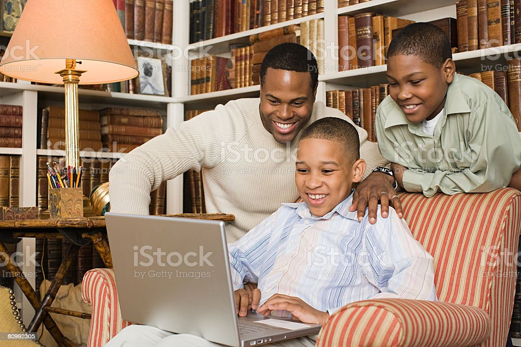 Father and sons looking at laptop royalty-free stock photo