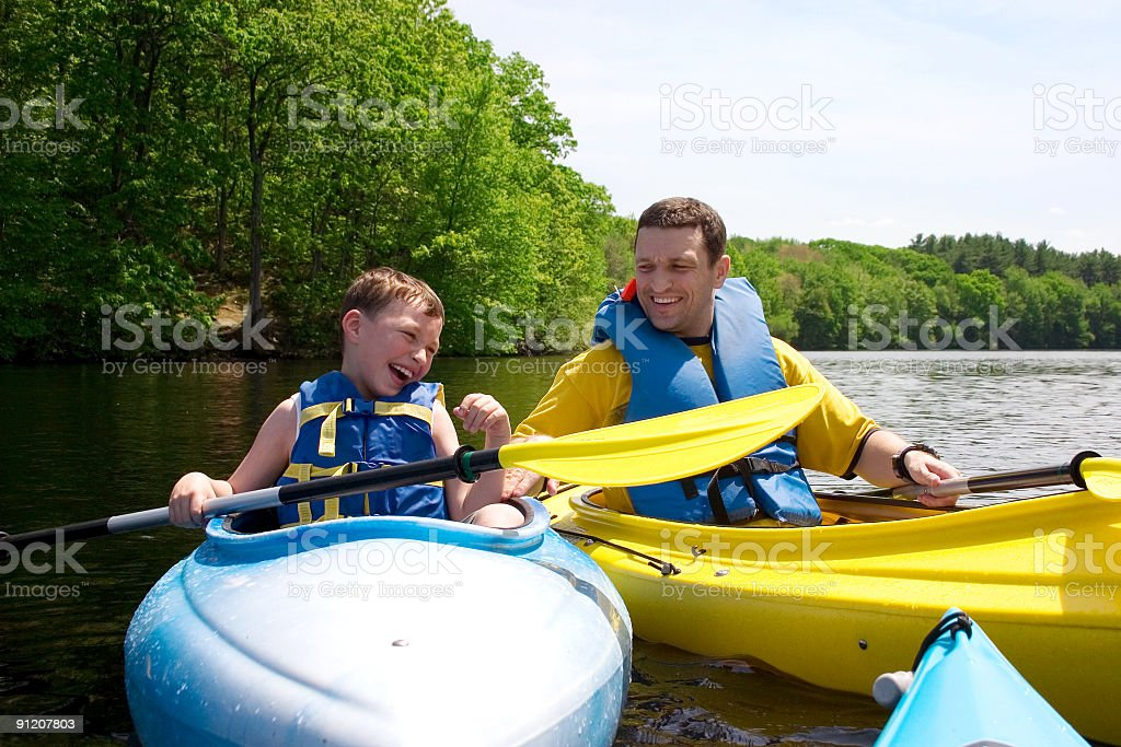 Father and sun smiling and kayaking royalty-free stock photo