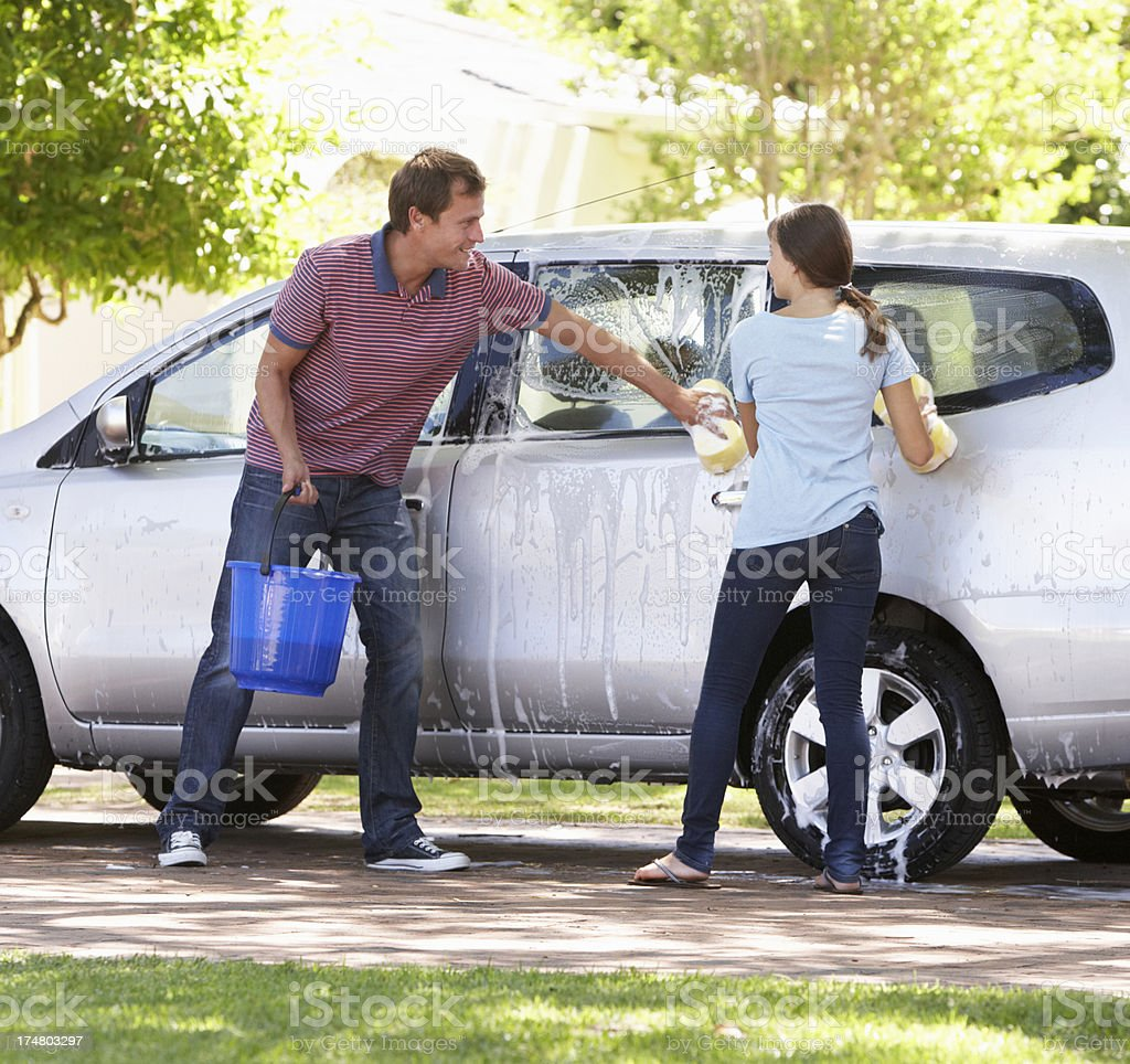 Father And Teenage Daughter Washing Car Together stock photo